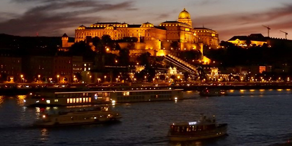 A photo of the Buda Castle in Budapest lit up with lights at dusk